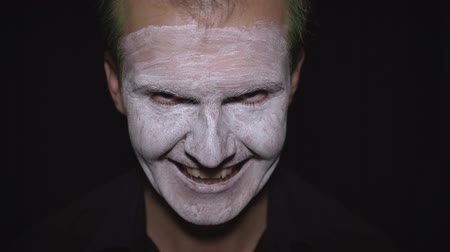 deguisement : Clown Halloween man portrait. Close-up of an crazy, evil clowns face. White face makeup. Green hair. Scary laugh. Attractive model in Halloween costume. Dark background