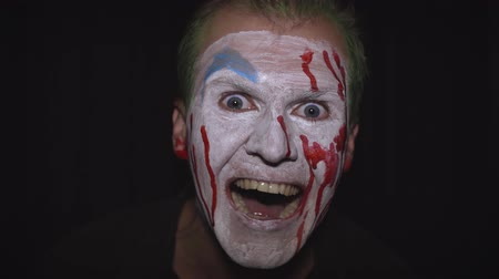 восхищенный : Clown Halloween man portrait. Close-up of crazy, evil clowns face with blood. White face makeup. Green hair. Scary laugh. Attractive model in Halloween costume. Dark background Стоковые видеозаписи