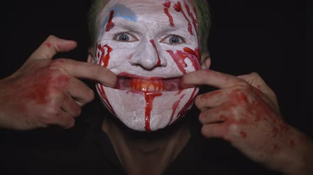 fobi : Clown Halloween man portrait. Close-up of crazy, evil clowns face with blood. White face makeup. Green hair. Scary smile with fingers. Attractive model in Halloween costume. Dark background Stok Video