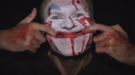 tréfacsináló : Clown Halloween man portrait. Close-up of crazy, evil clowns face with blood. White face makeup. Green hair. Scary smile with fingers. Attractive model in Halloween costume. Dark background Stock mozgókép