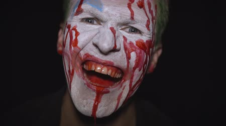 tréfacsináló : Clown Halloween man portrait. Close-up of crazy, evil clowns face with blood. White face makeup. Green hair. Scary laugh. Attractive model in Halloween costume. Dark background Stock mozgókép