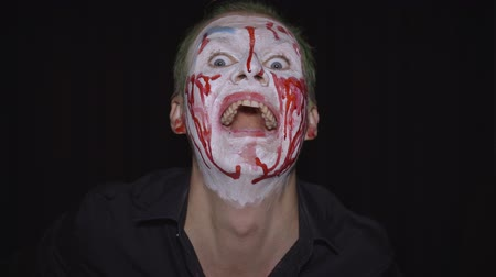 littekens : Clown Halloween man portrait. Close-up of crazy, evil clowns face with blood. White face makeup. Green hair. Scary laugh. Attractive model in Halloween costume. Dark background Stockvideo