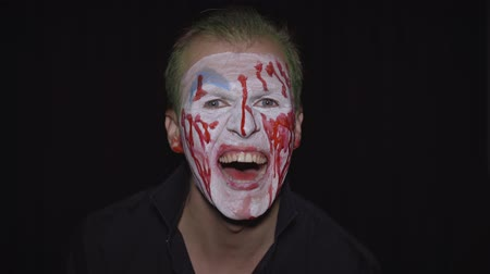 уродливый : Clown Halloween man portrait. Close-up of crazy, evil clowns face with blood. White face makeup. Green hair. Scary laugh. Attractive model in Halloween costume. Dark background Стоковые видеозаписи