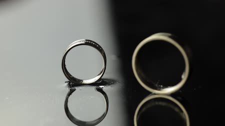 жених : Wedding rings on black and white water surface shining with light. Groom ring rolling to brides ring. Close up macro. Slow motion