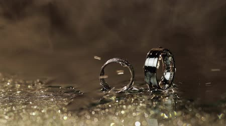 drahokamy : Wedding rings on dark water surface shining with light. Water mist. Fog. Rain, water drops. Close up macro. Slow motion