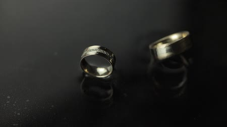 жених : Wedding rings on dark water surface shining with light. One of rings rotates. Water mist. Fog. Close up macro. Slow motion