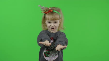 Happy beautiful little baby girl in a sweater with a snowman. Christmas concept. Makes fly air kisses. Positive, pretty, four years old child make faces and smile. Green screen. Chroma Key 動画素材