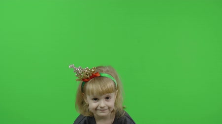 Happy beautiful little baby girl in a sweater with a snowman. Christmas concept. Makes fly air kisses and jumps. Positive, pretty, four years old child make faces and smile. Green screen. Chroma Key Stock mozgókép
