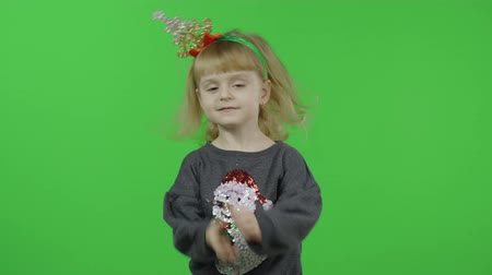 Happy beautiful little baby girl in a sweater with a snowman. Christmas concept. Positive, pretty, four years old child make faces and smile. Green screen. Chroma Key