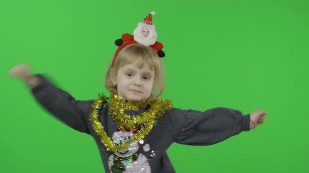 kardan adam : Happy beautiful little baby girl in a sweater with a snowman. Christmas concept. Makes fly air kisses. Positive, pretty, four years old child make faces and smile. Green screen. Chroma Key Stok Video