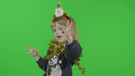 Happy beautiful little baby girl in a sweater with a snowman. Christmas concept. Ok. Positive, pretty, four years old child make faces and smile. Green screen. Chroma Key