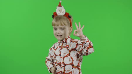 świety mikołaj : Happy beautiful little baby girl in a shirt with a Santa Claus. Christmas concept. Ok. Positive, pretty, four years old child make faces and smile. Green screen. Chroma Key Wideo