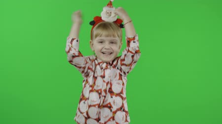 świety mikołaj : Happy beautiful little baby girl in a shirt with a Santa Claus. Christmas concept. Waving her hands. Positive, pretty, four years old child make faces and smile. Green screen. Chroma Key