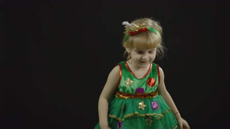 świety mikołaj : Happy beautiful little baby girl in christmas tree costume. Christmas concept. Positive, pretty, four years old child make faces, dance and smile. Black background