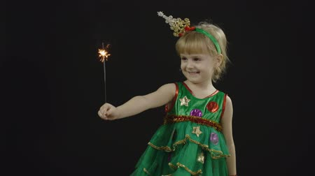 Happy beautiful little baby girl in christmas tree costume with burning Bengal lights. Christmas concept. Positive, pretty, four years old child make faces, dance and smile. Black background