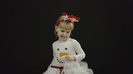 Happy beautiful little baby girl in snowman costume. Christmas concept. Positive, pretty, four years old child make faces, dance and smile. Black background