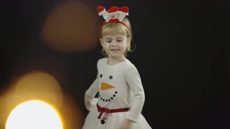 świety mikołaj : Happy beautiful little baby girl in snowman costume. Christmas concept. Positive, pretty, four years old child make faces, dance and smile. Black background
