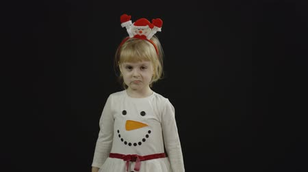 świety mikołaj : Happy beautiful little baby girl in snowman costume. Christmas concept. Ok. Positive, pretty, four years old child make faces, dance and smile. Black background