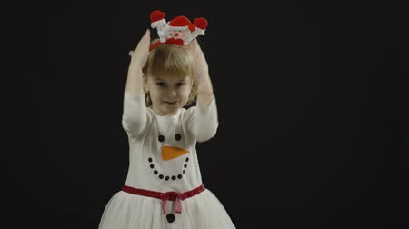 curioso : Happy beautiful little baby girl in snowman costume. Christmas concept. Positive, pretty, four years old child make faces, dance and smile. Black background