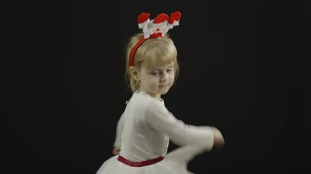 好奇心 : Happy beautiful little baby girl in snowman costume. Christmas concept. Positive, pretty, four years old child make faces, dance and smile. Black background