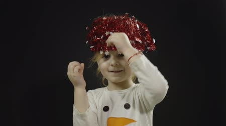 świety mikołaj : Happy beautiful little baby girl in snowman costume. Christmas decorations on the head. Positive, pretty, four years old child make faces, dance and smile. Black background Wideo