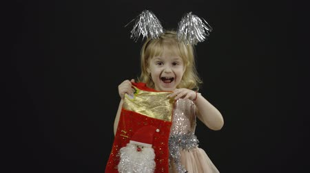 Happy beautiful little baby girl in glossy dress. Christmas concept. Positive, pretty, four years old child make faces, dance and smile. Black background