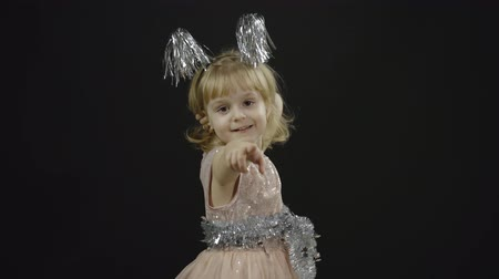 Happy beautiful little baby girl in glossy dress emotionally points at something with her hands. Christmas concept. Positive, pretty, four years old child make faces, dance and smile. Black background
