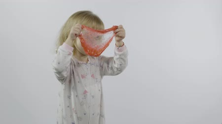Child having fun making ping slime. Kid playing with hand made toy slime. Funny kid girl. Relax and Satisfaction. Oddly satisfying pink slime for pure fun and stress relief. White background 影像素材