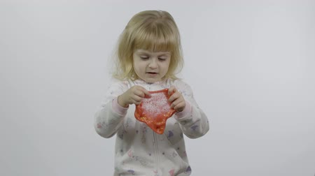 Child having fun making ping slime. Kid playing with hand made toy slime. Funny kid girl. Relax and Satisfaction. Oddly satisfying pink slime for pure fun and stress relief. White background 動画素材