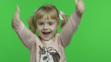 Positive girl in unicorn sweatshirt. Thumbs up. Happy four years old girl. Pretty little blonde child. Make faces and smile. Green screen. Chroma Key Stock mozgókép