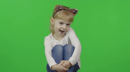 Girl in jeans and headband with a cats ears. Happy four years old girl. Pretty little blonde child. Make faces and smile. Green screen. Chroma Key