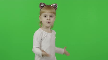 Girl in headband with a cats ears dance and sing. Happy four years old girl. Pretty little blonde child. Make faces and smile. Green screen. Chroma Key