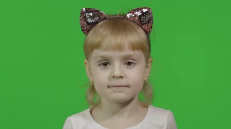 Girl in headband with a cats ears shows emotion of amazement. Happy four years old girl. Pretty little blonde child. Make faces and smile. Green screen. Chroma Key