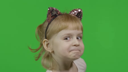 Girl in headband with a cats ears shows emotion of dissatisfied. Happy four years old girl. Pretty little blonde child. Make faces and smile. Green screen. Chroma Key