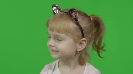 Girl in headband with a cats ears emotionally winks. Happy four years old girl. Pretty little blonde child. Make faces and smile. Green screen. Chroma Key