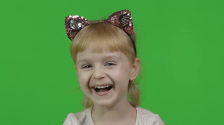 Girl in headband with a cats ears emotionally laughs loudly. Happy four years old girl. Pretty little blonde child. Make faces and smile. Green screen. Chroma Key 影像素材