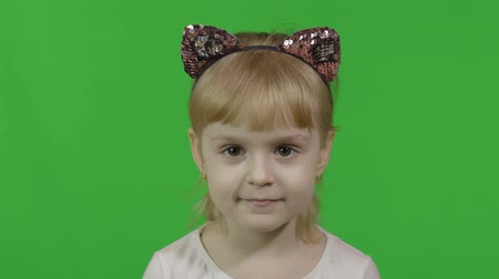 Girl in headband with a cats ears looks at camera. Happy four years old girl. Pretty little blonde child. Make faces and smile. Green screen. Chroma Key 動画素材