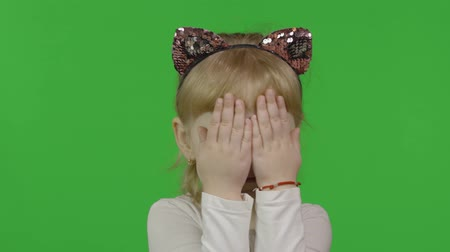 Girl in headband with a cats ears hides face behind hands. Happy four years old girl. Pretty little blonde child. Make faces and smile. Green screen. Chroma Key 動画素材