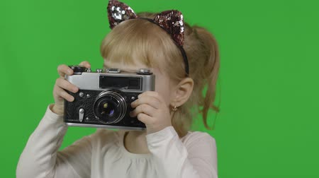 Girl in headband with a cats ears taking pictures on an old camera. Happy four years old girl. Pretty little blonde child. Make faces and smile. Green screen. Chroma Key
