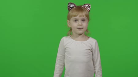 Girl in headband with a cats ears emotionally points at something with her hands. Happy four years old girl. Pretty little blonde child. Make faces and smile. Green screen. Chroma Key