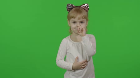 Girl in headband with a cats ears. Nose picking. Happy four years old girl. Pretty little child, 4 year old blonde girl. Make faces and smile. Green screen. Chroma Key 動画素材