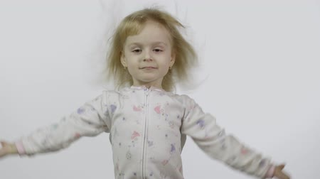frizura : Little girl in pajama with funny headdress is fooling around and make faces. White background. Concept: Freedom, happiness, childhood. Happy four years old, pretty little blonde child Stock mozgókép