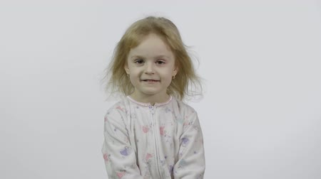Little beautiful baby girl in pajama looking at camera. White background. Concept: Freedom, happiness, childhood. Happy four years old, pretty little blonde child