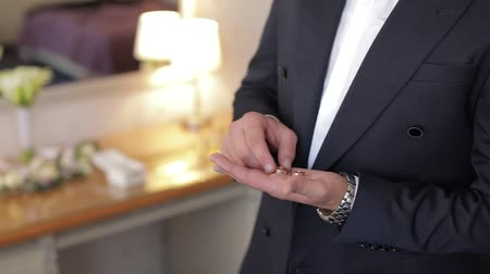 луки : Handsome groom holds wedding rings in his hand. Wedding morning. Businessman. Slow motion