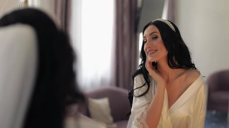 новобрачный : Beautiful and lovely bride in night gown and veil looks in the mirror and does makeup. Pretty and well-groomed woman. Wedding morning. Slow motion