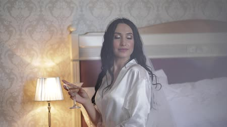 preparált : Beautiful and lovely bride in night gown and veil with glass of martini. Pretty and well-groomed woman sitting on a bed. Wedding morning. Slow motion