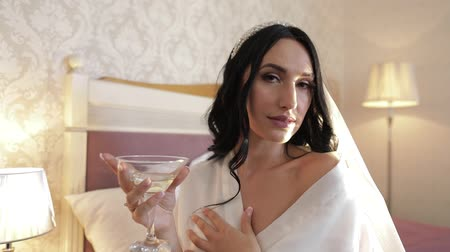 новобрачный : Beautiful and lovely bride in night gown and veil with glass of martini. Pretty and well-groomed woman sitting on a bed. Wedding morning. Slow motion