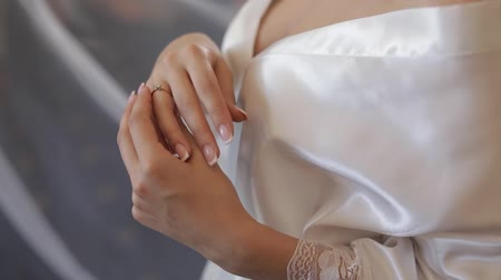 новобрачный : Beautiful and lovely bride in night gown touches her engagement ring. Close-up shot. Wedding morning. Slow motion
