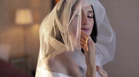 lakodalom : Beautiful and lovely brunette bride in night gown and veil. Close-up shot. Pretty and well-groomed woman sitting on a bed. Wedding morning. Slow motion
