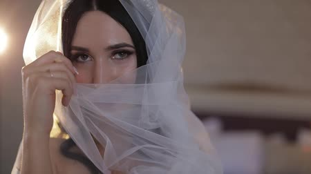 новобрачный : Beautiful and lovely brunette bride in night gown and veil. Close-up shot. Pretty and well-groomed woman sitting on a bed. Wedding morning. Slow motion